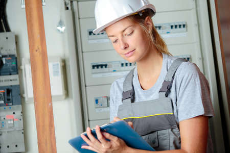 Female electrician writing on clipboard
