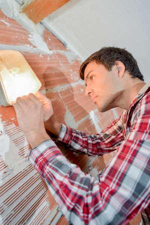wall lamp: man putting a wall lamp