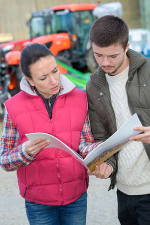 saleswoman convincing young famrer to buy new agricultural machinery Stock Photo