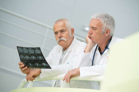Senior medics looking puzzled over xray