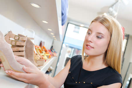 blonde females: Lady holding shoe in shop Stock Photo