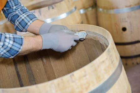 cooper: Cooper making wooden barrel