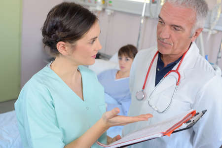 confer: Doctor and nurse in discussion at patients bedside