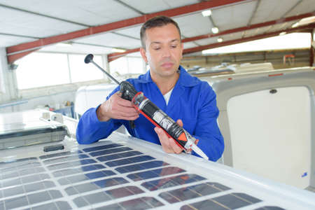 Man applying sealant around solar panel