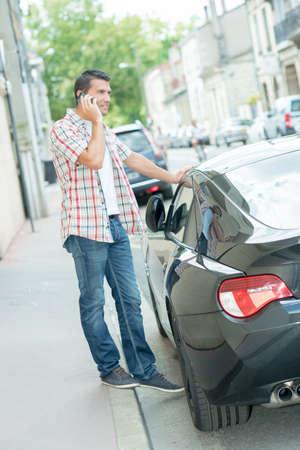 sidewalk talk: Man leaning up against his car