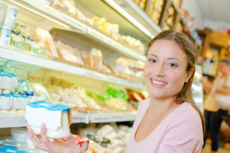 buying: Woman buying yoghurt Stock Photo