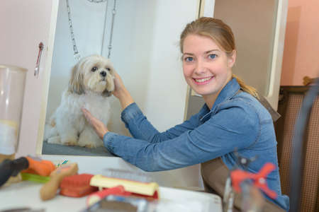 behave: pet groomer posing with the dog