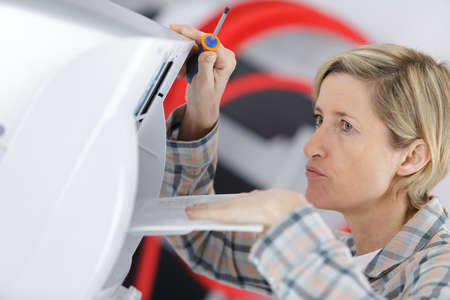 blonde handywoman cleaning fixing ventilation system Stock Photo
