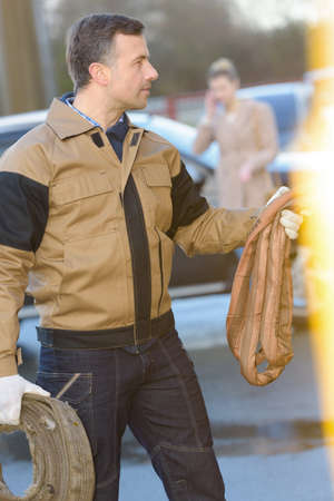 Uniformed man carrying reel of hose Stock Photo