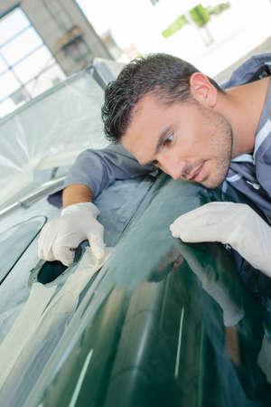 assessing: Mechanic assessing finish of classic car Stock Photo