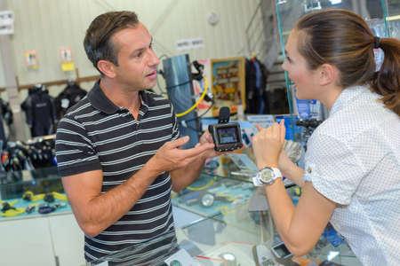 enquiring: Female customer enquiring abut electronic device in shop