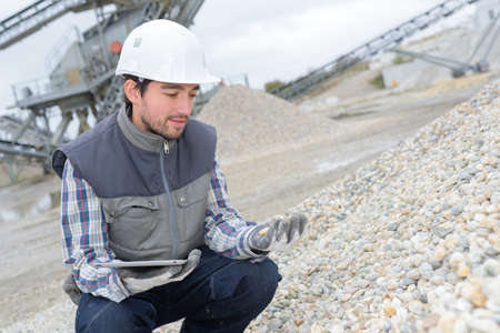 stone tablet: Man holding tablet looking at pile of stones in quarry