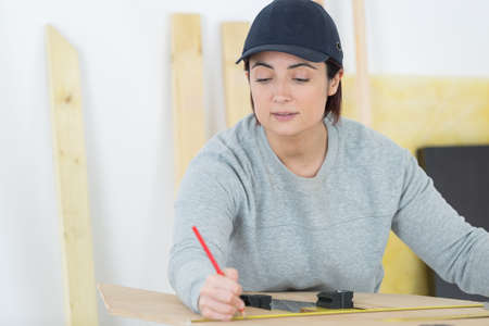 strip shirt: portrait of happy female woodworker drafting new project at workshop Stock Photo