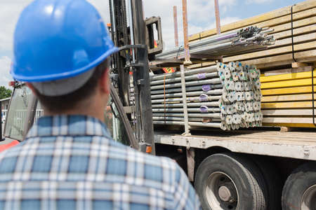 flatbed truck: Rear view of man looking at lorry load of materials