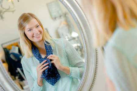 woman clothes: Lady trying on scarf, looking at reflection in mirror Stock Photo