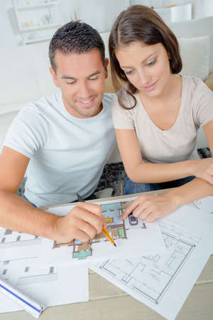 domestic life: Couple looking over plans for their new home