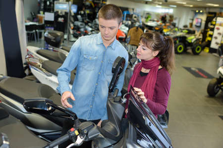 a two wheeled vehicle: Young couple looking at scooter Stock Photo