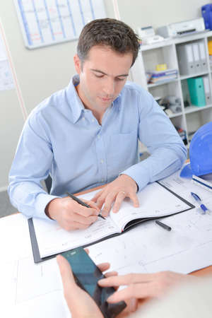 man at work: Man writing at his desk Stock Photo