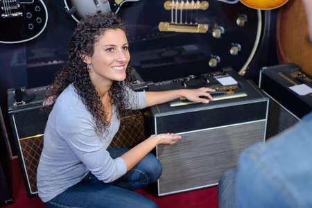 comercio: Señora que muestra amplificador al cliente Foto de archivo