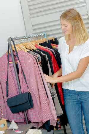 choose person: Lady browsing through rail of clothes
