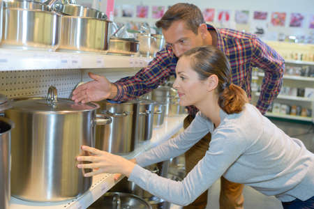 Man and woman looking at large saucepans on shop shelf Stock Photo
