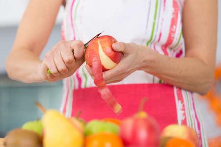 elder woman peeling apples in her kitchen