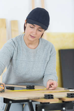 woman measuring a plywood Stock Photo