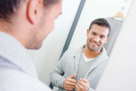 lapels: Man trying on jacket, looking at reflection in mirror