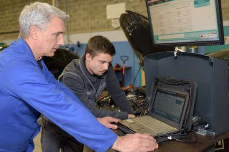 trainee: auto mechanic teacher and trainee performing tests at mechanic school Stock Photo