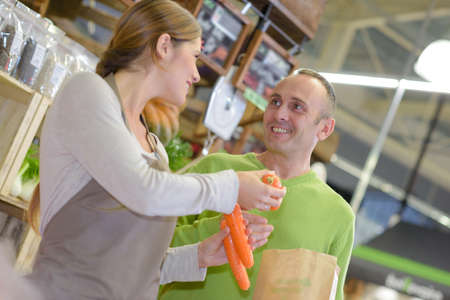 shop assistant: Shop assistant passing carrots to customer Stock Photo