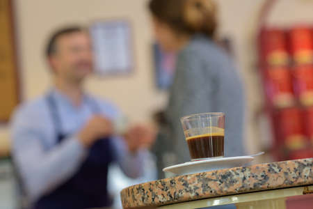 columbian: Espresso coffee in foreground, people behind Stock Photo