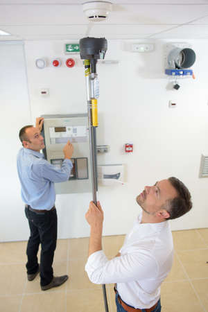 prototypes: product inspectors testing a smoke detector