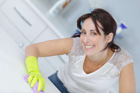 disinfecting: woman cleaning surface in kitchen Stock Photo