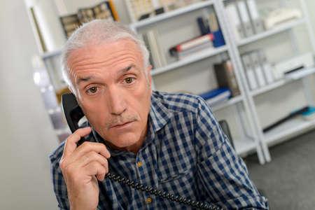 raised eyebrow: man on telephone, looking shocked