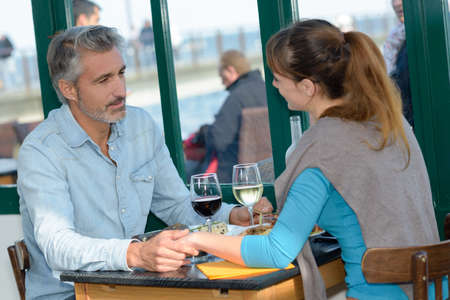intent: Couple holding hands across restaurant table