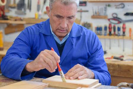 hobbyist: senior man working on his work bench
