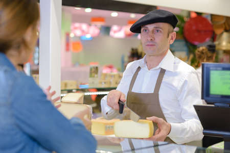 stereotypical: Man in French traditional dress serving cheese Stock Photo