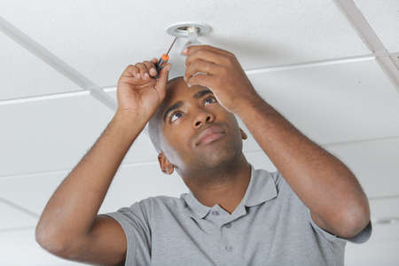 electric power: electrician fitting lightbulb in office