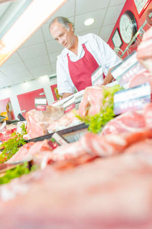 meat counter: Butcher behind meat counter