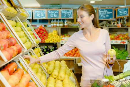 grocers: Young woman buying apples