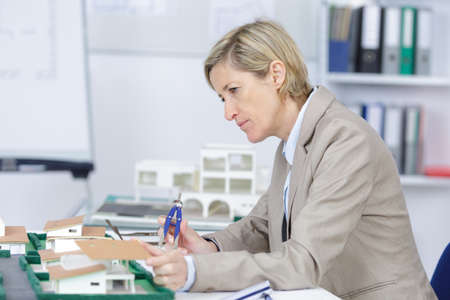 female architect: pensive experienced female architect at work in her office