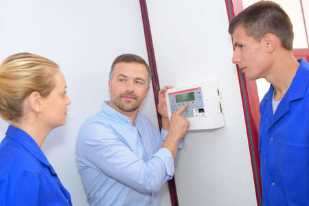 communication industry: Man showing students control panel on wall