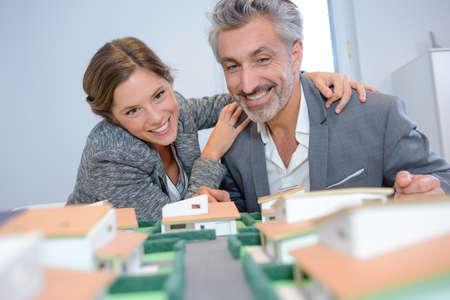 elation: Man and woman joyfully looking at model housing development Stock Photo