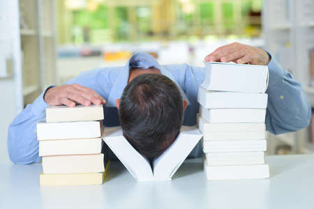 Man with his head between two piles of books
