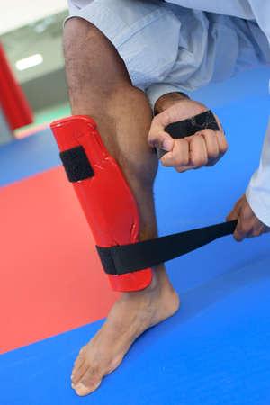 fierce competition: Martial artist putting on a leg guard