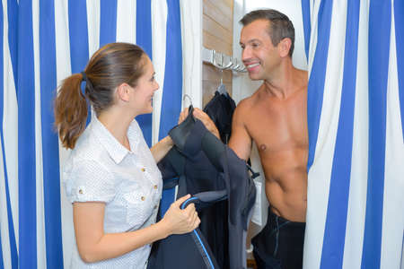 changing room: man trying on wetsuit in shop changing room