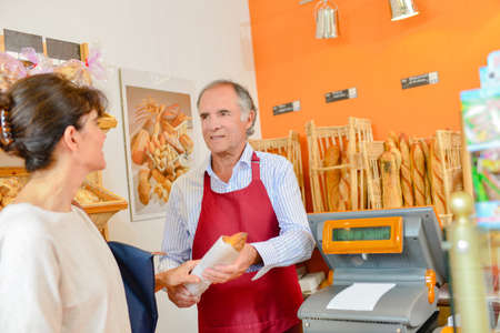serf: woman buying baguette Stock Photo