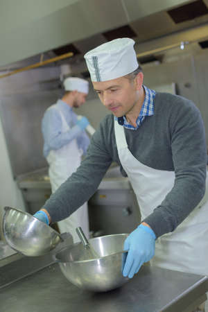 busy person: Chef pouring from one bowl to another