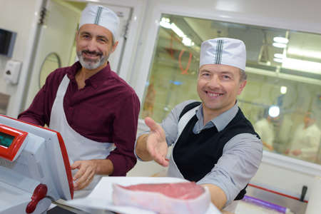 congenial: Two male butchers showing off their meat Stock Photo