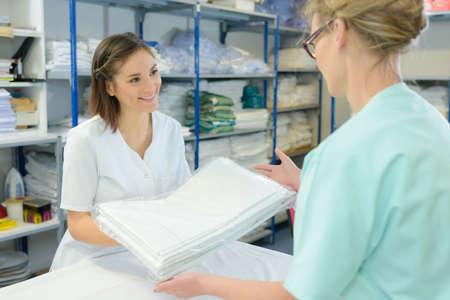 病院の洗濯物から清潔なシーツを取って看護師します。
